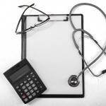 מחשבון, לוח כתיבה וסטטוסקופ של רופא העוסק בועדה רפואית לקביעת גמלת נכות מעבודה