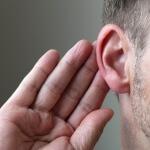 אדם חרש שמסמן עם היד שלו על האוזן