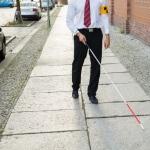 אדם עיוור הולך ברחוב בעזרת מקל נחייה